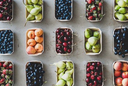 Flat lay of fresh fruits and berries over grey concrete background