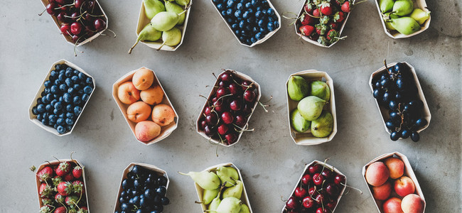 Various fruits and berries over grey concrete background  wide composition