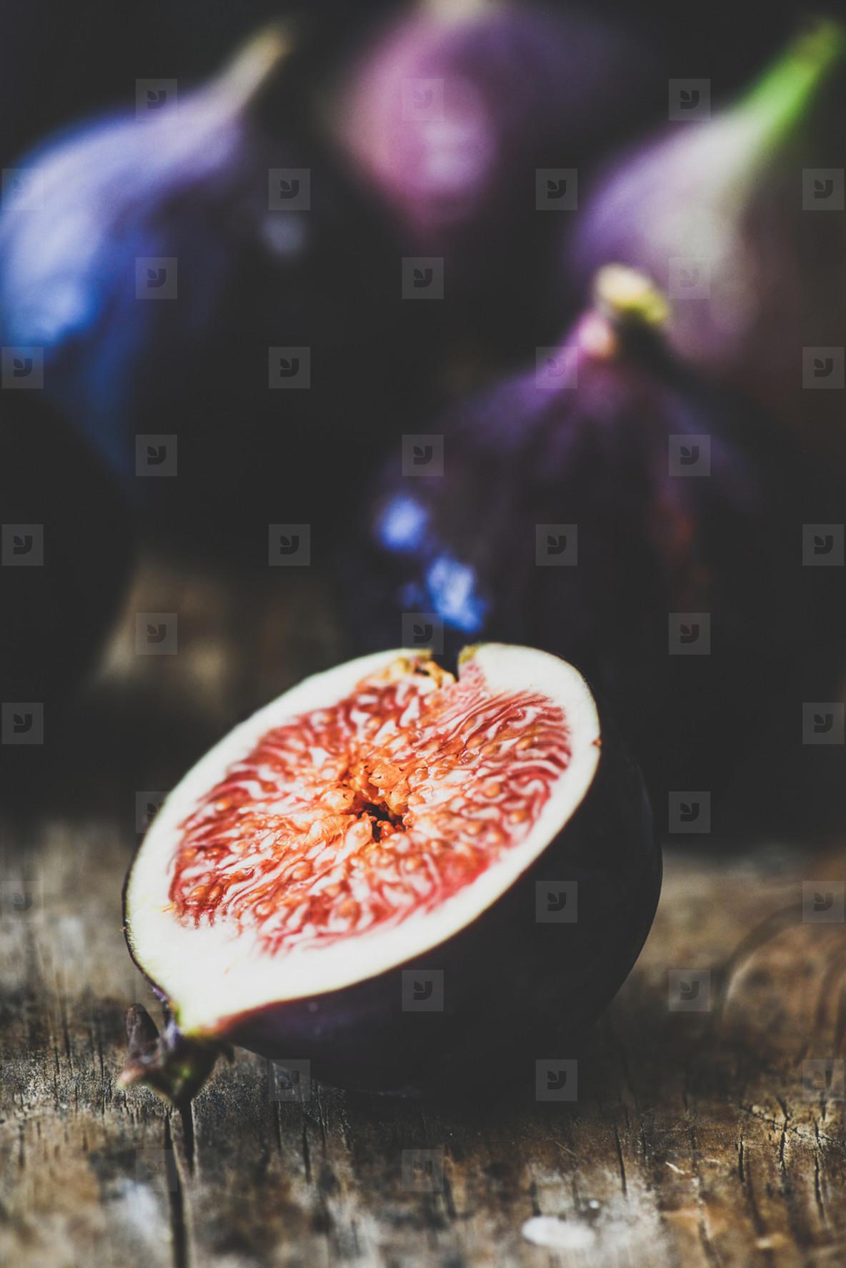 Fresh ripe seasonal purple fig cut over wooden board  close up