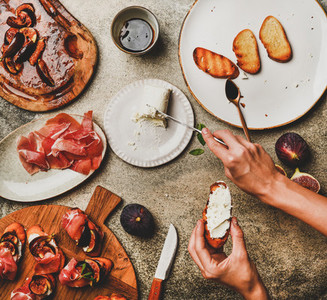 Crostini with prosciutto  figs and womans hands spreading cheese
