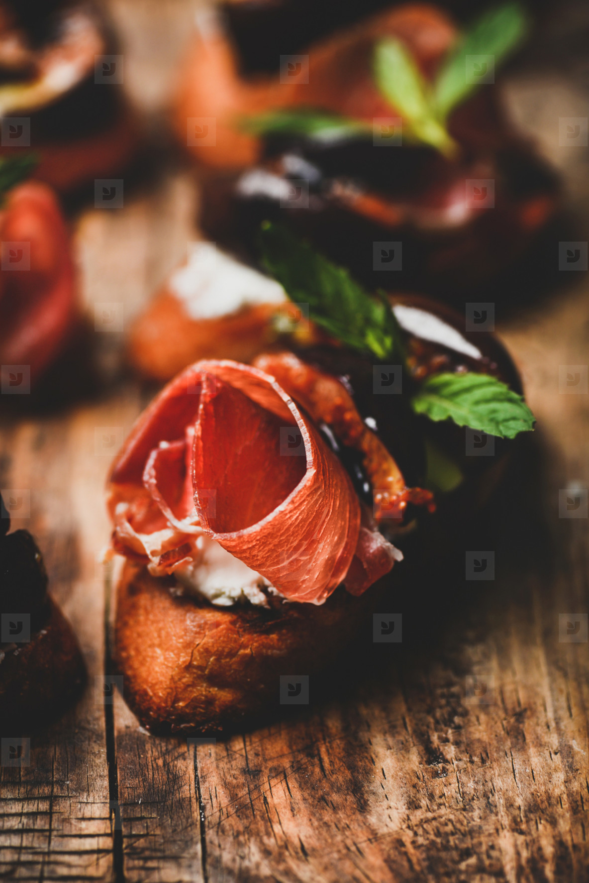 Crostini with prosciutto  goat cheese and figs on wooden board