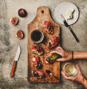 Crostini with prosciutto and glass of wine in womans hands