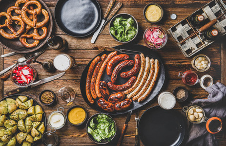 Flat lay of Bavarian Octoberfest dinner with beers and meat sausages