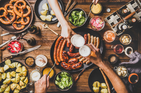 Flat lay of dinner table with beer  Bavarian sausages and snacks