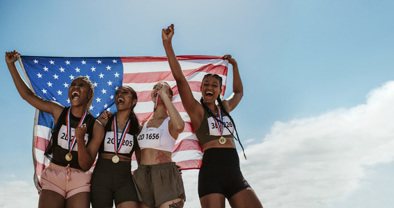 American female athletes celebrating a win holding flag
