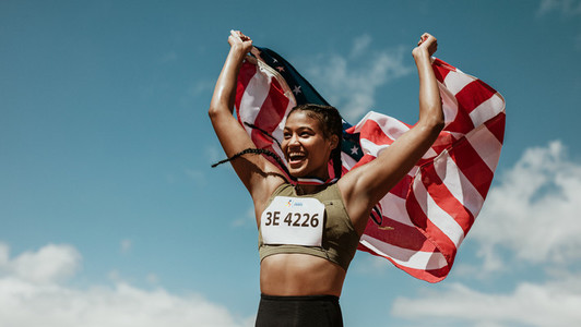 Runner celebrating victory outdoors holding the US flag