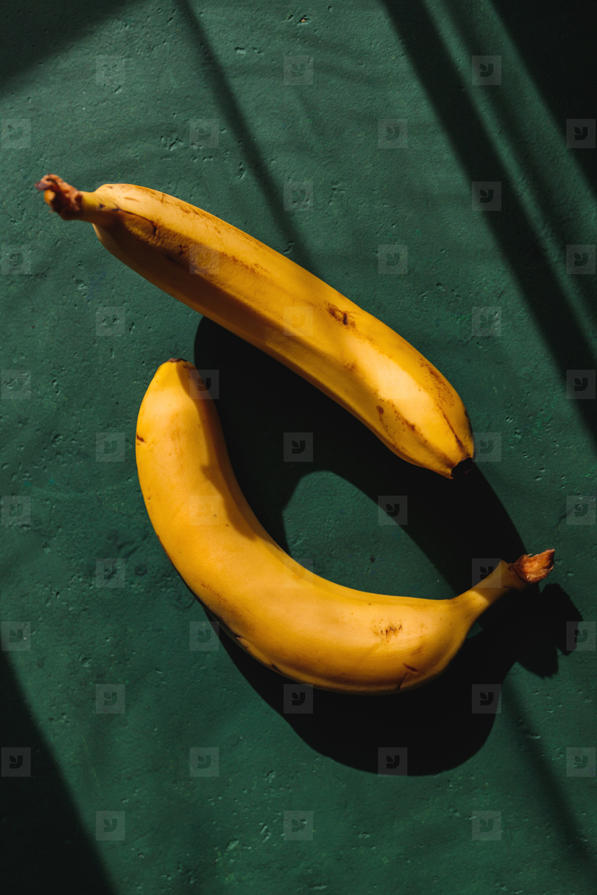 Bananas on a green background  Summer abstract creative photography with sun light and shadows