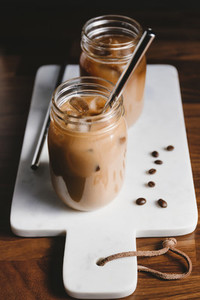 Two glass jars with iced latte on a white marble tray with eco metal tubes