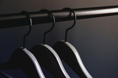 Grey hangers without clothes on a crossbar against black wall