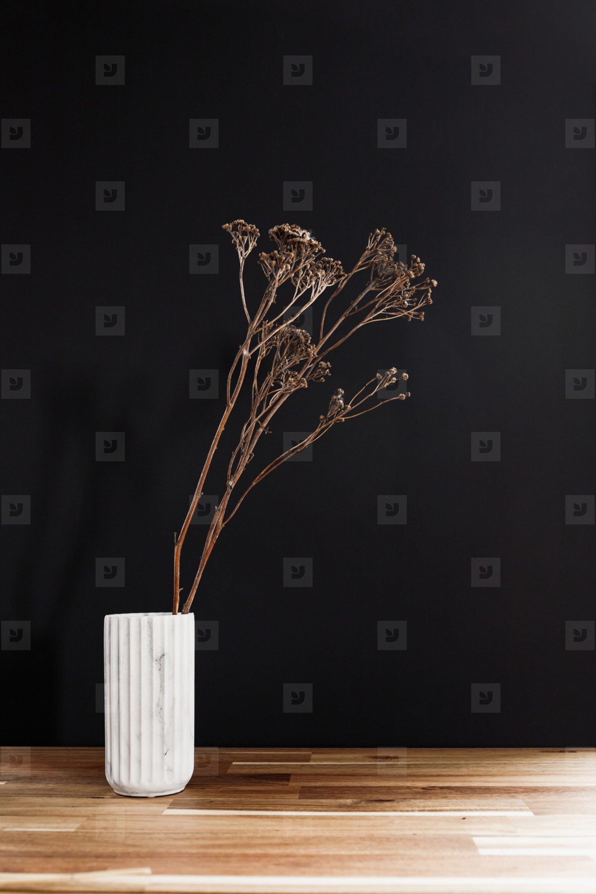 Dry decor plant in a white marble vase on a wooden table against black wall