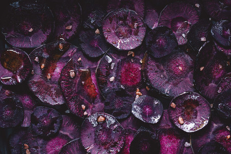 Slices of purple carrot with pink salt and olive oil for roasting Macro photography top view