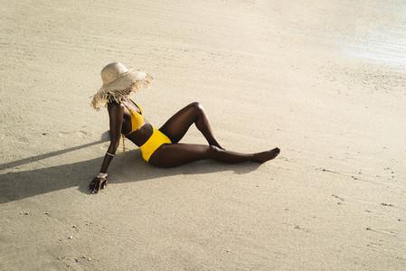 Woman in bikini with sun hat sitting on the beach