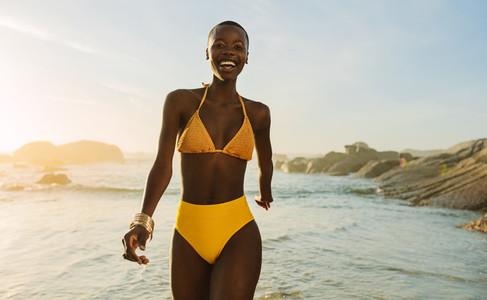 Attractive african woman in bikini walking on the beach