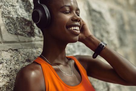 Runner enjoying listening music while having break