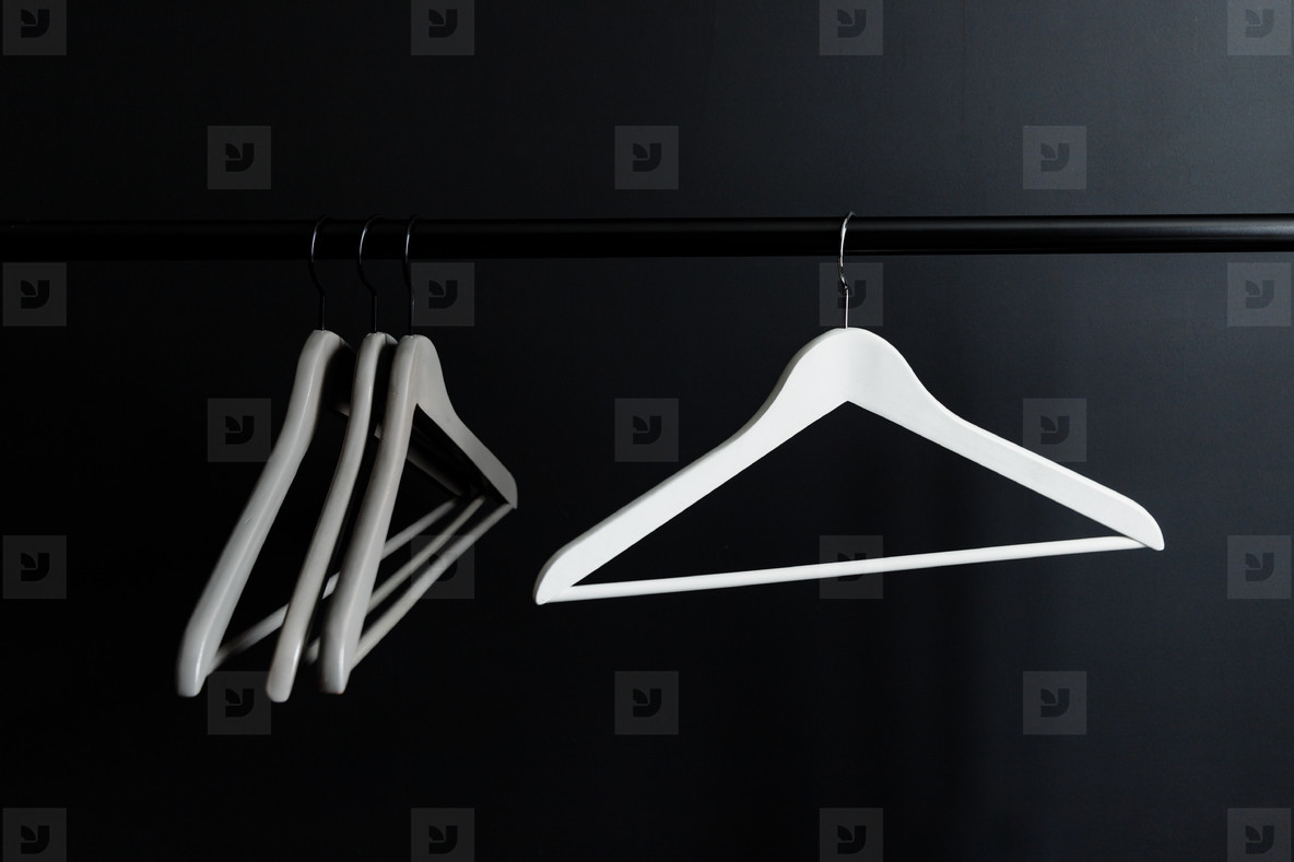 Hangers without clothes on a crossbar against black wall