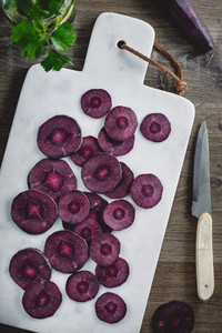 Overhead view on slices of raw purple carrot on a white marble board over kitchen table