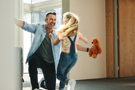 Girl running to greet her father returning from business trip