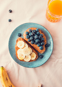 Two toasts with peanut butter  blueberry and banana on a blue plate over pink pastel background