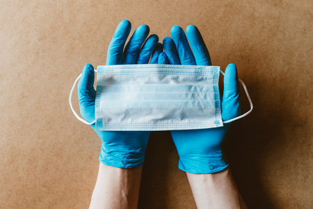 Hands in blue rubber gloves hold a medical mask Health care and antivirus protection concept top view