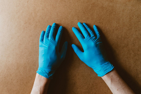Hands in blue protective rubber gloves over beige background Health care and antivirus concept top view