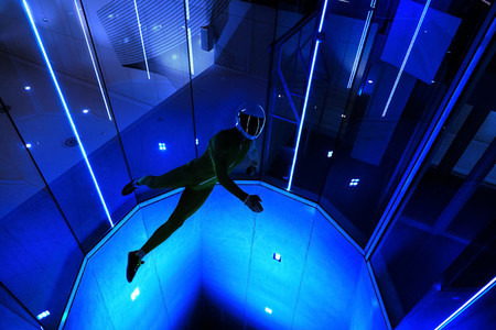 A man flier doing stunts in an indoor wind tunnel