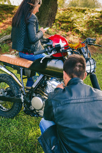 Man fixing his motorcycle while his girlfriend looks at mobile