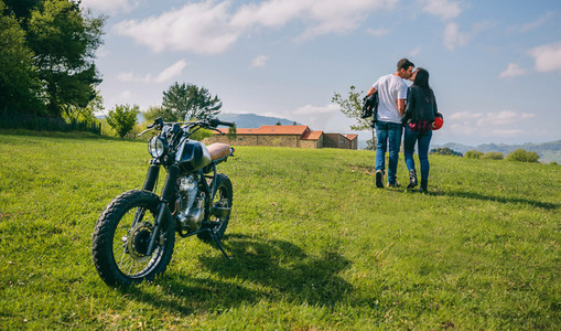 Couple kissing and walking on the field with motorbike