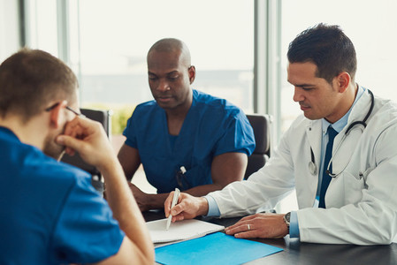 Doctor in white coat on staff meeting
