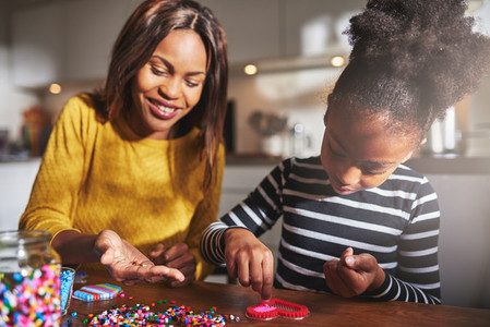 Cheerful woman holding beads for child at table