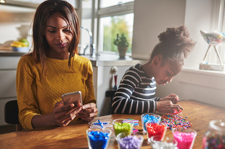 Parent checking phone while girl makes crafts
