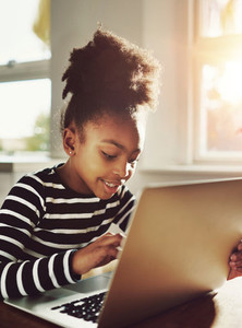 Young Black Girl Chatting to Someone Using Laptop