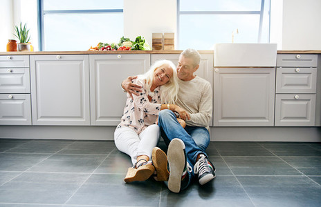 Loving couple sitting on kitchen floor