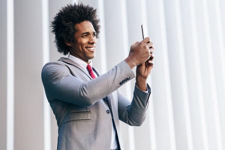 Black Businessman using a smartphone near an office building