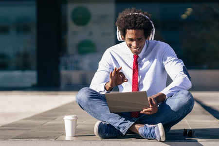 Black Businessman using laptop computer and headphones