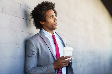 Black Businessman taking a coffee break with a take away glass