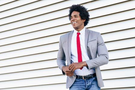 Happy Black Businessman wearing suit dancing outdoors