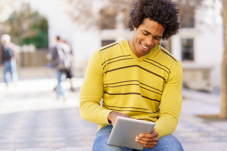 Black man using a digital tablet sitting on a bench outdoors