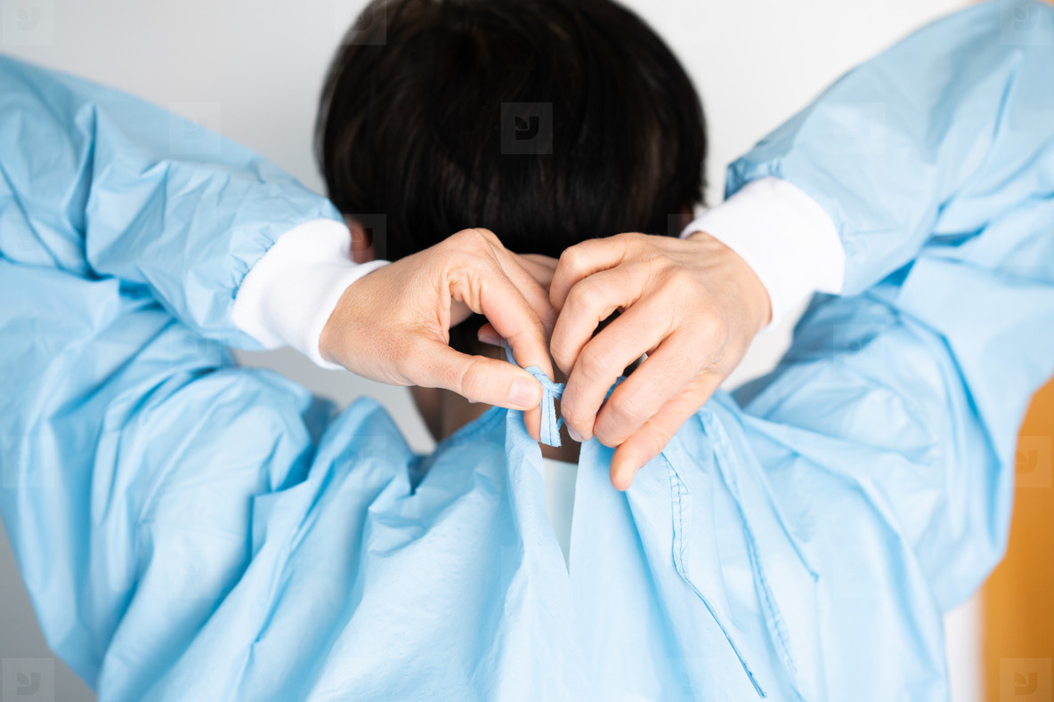 Middle aged doctor putting on a protective gown