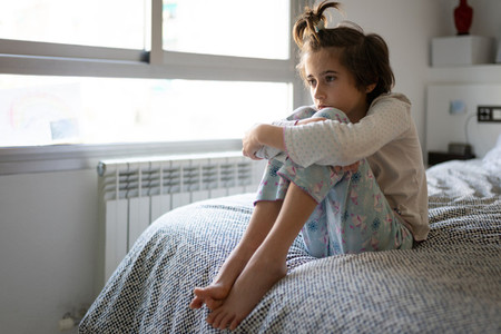 Nine year old girl sitting in bed bored by confinement