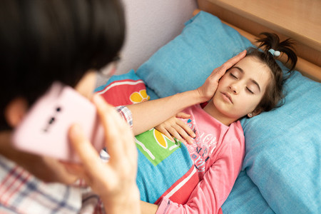 Mother worried about her daughters temperature calling the doctor