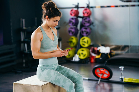 Woman consulting her training on her smartphone sitting in a jump box