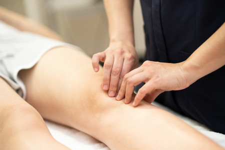 Physiotherapist woman doing a treatment on a womans knee