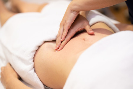 Woman receiving a belly massage in a physiotherapy center
