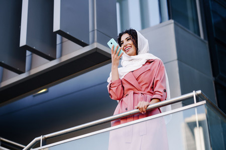 Muslim Woman with hijab recording voice note with a smartphone