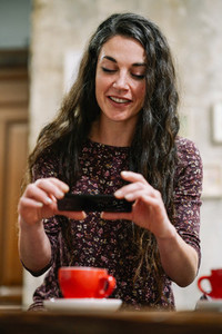 Young woman with some gray hair using smartphone in a cafe