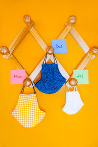 Surgical masks of family hanging on the coat rack with labels