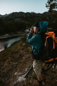 Hiker photographing scenic view