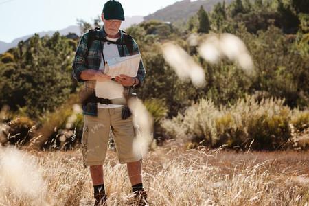 Senior hiker using map