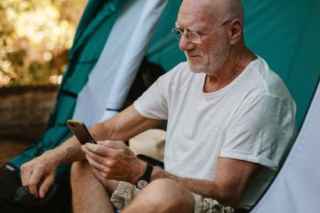 Senior man using phone at campsite