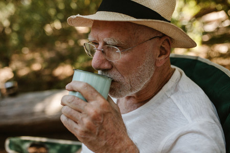 Senior man having refreshing coffee at campsite
